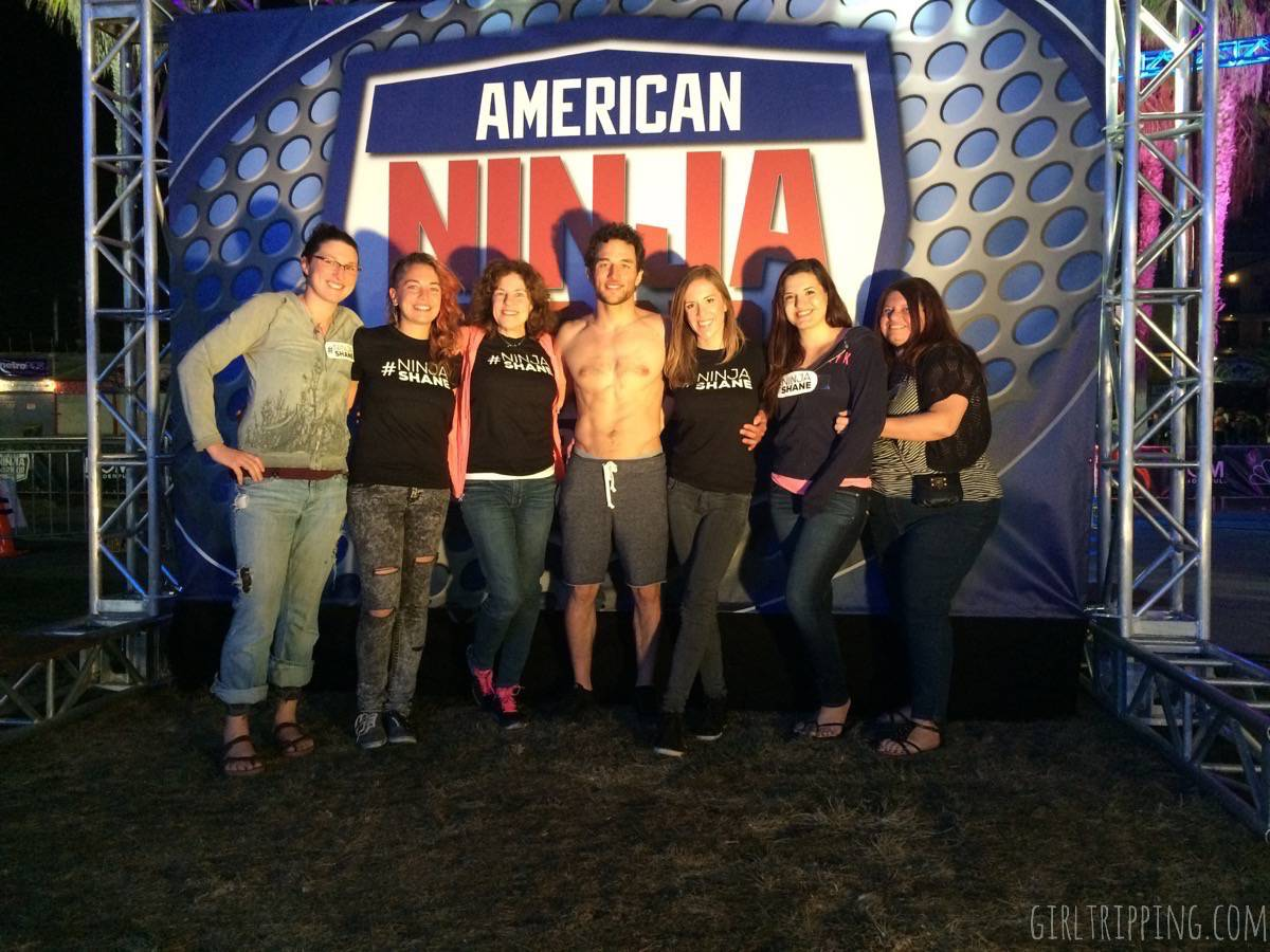 American Ninja Warrior tryouts in front of show logo with family - https://girltripping.com
