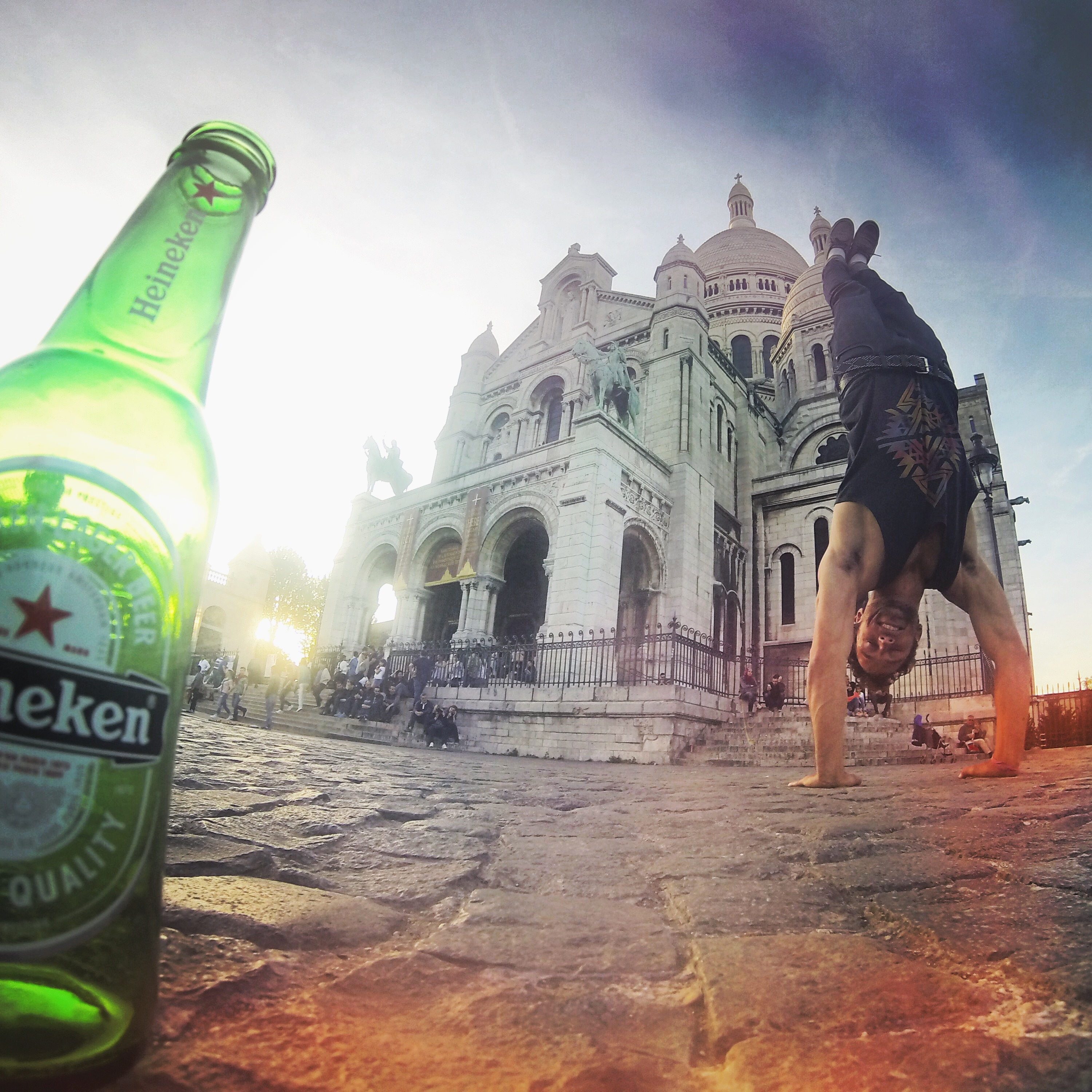 Shane doing a handstand with a beer in front of Sacred Heart church