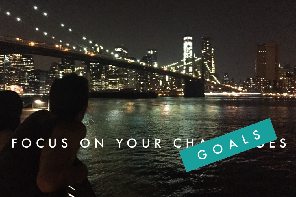 Silhouette looking at New York at night with a lighted bridge - text: Focus on your goals, not your challenges""